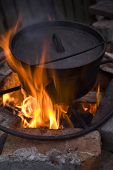 stock photo of dutch oven  - Cooking in a Dutch Oven over a fire - JPG