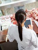 Rear view of female butcher using digital tablet in butchery