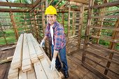 Portrait of smiling carpenter measuring wooden plank with tape in cabin at construction site