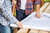 pic of carpenter  - Midsection of male and female carpenters analyzing blueprint at site - JPG