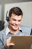 Smiling customer service representative wearing headset while holding clipboard in office