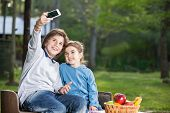 Smiling siblings taking selfportrait through smartphone at campsite