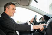 image of only mature adults  - Side view of cheerful mature man in formalwear driving car and touching dashboard with finger - JPG