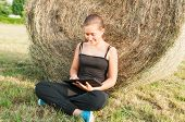 image of haystack  - Lovely young girl with device siting on the field close to haystack - JPG