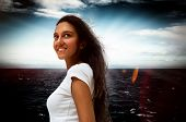 Smiling attractive young Indian woman standing looking up into the air with a dreamy expression against a dark dramatic sea in a mystical portrait