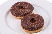 Two Donuts With Chololate Glaze On White Plate