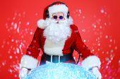 Santa Claus DJ near brilliant sparkling disco ball. Christmas celebration.