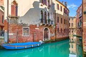 Boat on narrow canal among old brick houses in Venice, Italy.