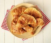 Fresh homemade croissant in a plate on a wooden background