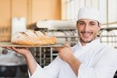 Baker holding a freshly baked loaf in the kitchen of the bakery