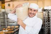 Smiling baker holding bag of rising dough in the kitchen of the bakery