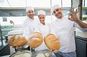 Team of bakers smiling at camera holding bread in the kitchen of the bakery