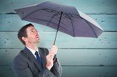 Businessman sheltering under black umbrella against painted blue wooden planks
