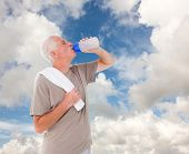 Senior man drinking from water bottle against blue sky with white clouds