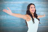 Carefree brunette with arms out against wooden planks