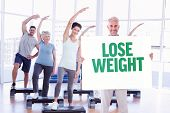 Smiling man showing large poster against lose weight