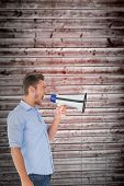 Angry man shouting through megaphone against wooden planks