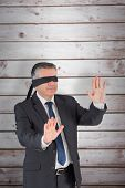 Mature businessman in a blindfold against wooden planks