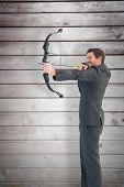Businessman shooting a bow and arrow against wooden planks