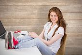 Pretty redhead with feet up on desk against wooden surface with planks