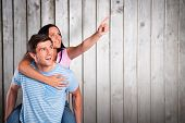 Young man giving girlfriend a piggyback ride against wooden planks