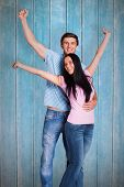 Young couple cheering at camera against wooden planks