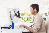 Casual business people around conference table in office against casual businessman working at his desk