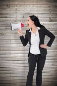 Pretty businesswoman shouting with megaphone against wooden planks background