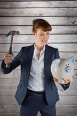 Businesswoman breaking piggy bank against wooden planks