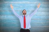 Happy cheering businessman raising his arms against wooden planks