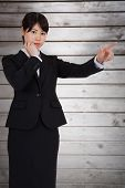 Thoughtful businesswoman pointing against wooden planks