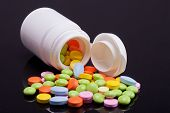 Lot Of Colorful Pills With White Box On Black Background