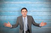 Businessman posing with hands out against wooden planks