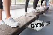 The word gym and womens feet stepping in aerobics class against badge
