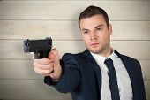 Serious businessman pointing a gun against bleached wooden planks background