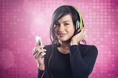 Charming happy girl enjoying listening to music with headphones and mp3 player, isolated on pink disco background.