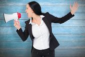 Pretty businesswoman shouting with megaphone against wooden planks