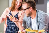 Woman and man cooking spaghetti in domestic kitchen
