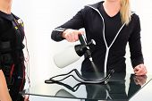 foto of stimulation  - Female coach prepare ems electro muscular stimulation costume  - JPG