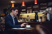 Young attractive businessman in a suit drinking coffee and using tablet to read news