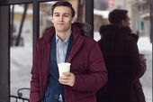 Young businessman in winter coat takes coffee to go a cafe.