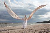 Female Model In Extreme Long Beige Dress Posing Dynamic In The Beach. Waving Fabric. Fluttering Long