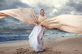 Fashionable Model Posing In Extremely Long Dress On The Seashore