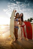 Two young ladies surfers standing with boards on the beach and showing shaka signs
