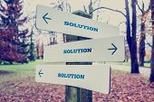 picture of solution  - Retro effect faded and toned image of a rural signboard with the word Solution with arrows pointing in three directions - JPG