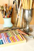 Paintbrushes with colorful chalk pastels in box on wooden background