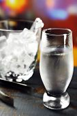 Glass of water with ice on wooden table and bright blurred background