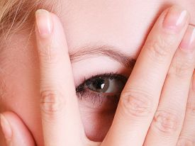 stock photo of shy woman  - Closeup of afraid frightened woman peeking through her fingers - JPG