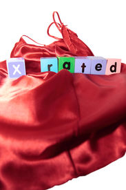 picture of x-rated  - x rated written with blocks on a silk nightie against white background