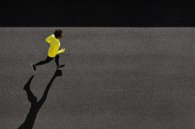 pic of sprinters  - Top view athlete runner training at black road in yellow sportswear - JPG